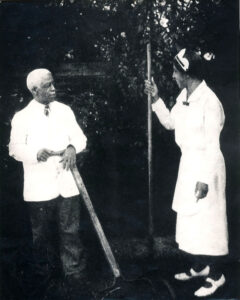 Isaac and Mary Scott holding garden tools in a garden